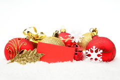 Goldene, rote Weihnachtsdekoration auf Schnee mit Wunschkarte Lizenzfreies Stockbild