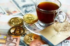 Goldene Schlüsselwährungsmünze Bitcoin auf Dollar, Eurobanknoten Hintergrund und Kreditkarte nahe Tasse Kaffee investitionen stockbilder