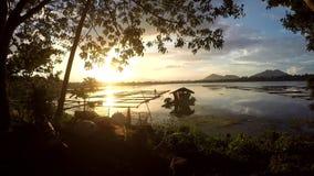 Goldene Sonne, die über AquaFischzucht-Bambusstrukturen auf Gebirgssee einstellt stock video footage
