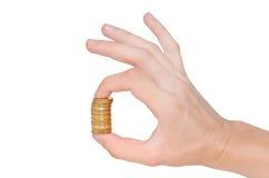 Goldene Spaltenmünzen und -hand lizenzfreie stockbilder