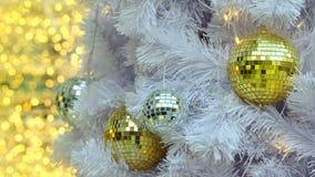 Goldene Spiegel Weihnachtsballeinzelteile auf weißer Torte und gelbem bokeh bilden LED-Beleuchtungshintergrund Stockbild