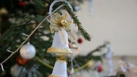 Goldene Spielzeugglocken hängen am Weihnachtsbaum unter dem Blinken von farbigen Girlanden, Nahaufnahme stock video footage