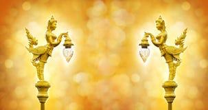 Goldene Statue des Engelsgriffs die Lampe auf dem bokeh Hintergrund Stockfotografie