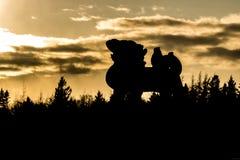 Goldene Statue silhouettiert bei Sonnenuntergang Stockbild