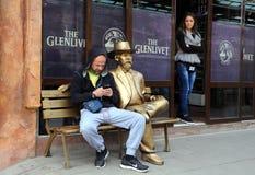 Goldene Statue und zwei Leute Stockfotos