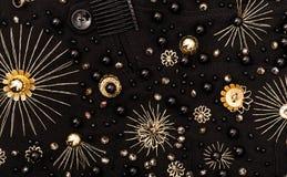 Goldene Stickerei von Blumen und von schwarzen Perlen auf Gewebe Stockbild