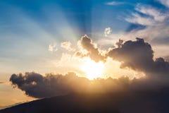 Goldene Strahlen der Sonne durch die dunklen Wolken Stockbilder