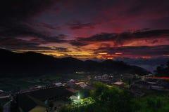 Goldene Stunde des schönen Sonnenuntergangs im Hügel mit Dorf Lizenzfreie Stockfotografie