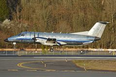 Goldene Stundenlandung des kleinen Flugzeuges des Aluminiumkörperdoppelpropeller-Frachters stockfotos