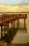 Goldene Sun-Sätze auf See und Pier stockbild