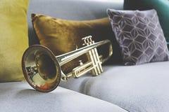 Goldene Trompete, die auf grauem Sofa liegt stockfotografie