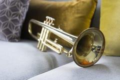 Goldene Trompete, die auf grauem Sofa liegt stockfoto