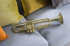 Goldene Trompete, die auf grauem Sofa liegt lizenzfreie stockbilder