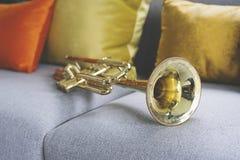 Goldene Trompete, die auf grauem Sofa liegt stockfotos