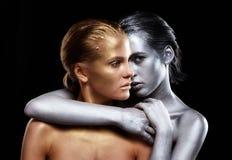 Goldene und silberne Mädchen auf schwarzem Hintergrund Silbernes weibliches huggi Stockfoto