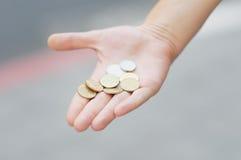 Goldene und silbrige Münzen (Schekel) in der Hand Stockbild