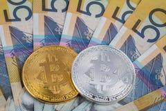 Goldene und Splitter bitcoins auf Stapel des Australiers Nahaufnahme mit 50 Dollarbanknoten Lizenzfreies Stockfoto