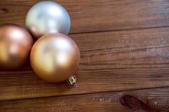 Goldene Weihnachtsbälle auf dem Holztisch stockbilder