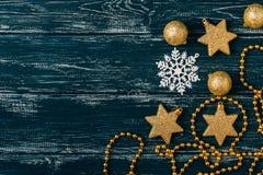 Goldene Weihnachtsbälle und eine Schneeflocke auf einem blauen alten hölzernen Hintergrund Raum für Text Abstraktes Hintergrundmu Stockbild