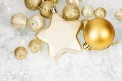 Goldene Weihnachtsbälle und -stern auf eisigem Hintergrund stockbilder