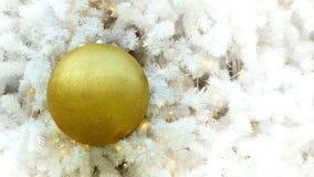 Goldene Weihnachtsballeinzelteile auf weißer Torte und gelbem bokeh bilden LED-Beleuchtungshintergrund Lizenzfreie Stockbilder