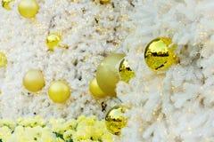 Goldene Weihnachtsballeinzelteile auf weißer Torte und gelbem bokeh bilden LED-Beleuchtungshintergrund Stockbild