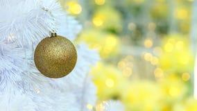 Goldene Weihnachtsballeinzelteile auf weißer Torte und gelbem bokeh bilden LED-Beleuchtungshintergrund Lizenzfreies Stockfoto