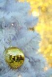 Goldene Weihnachtsballeinzelteile auf weißer Torte und gelbem bokeh bilden LED-Beleuchtungshintergrund Lizenzfreie Stockfotografie