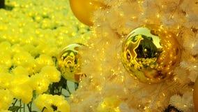 Goldene Weihnachtsballeinzelteile auf weißer Torte und gelbem bokeh bilden LED-Beleuchtungshintergrund Lizenzfreie Stockfotos