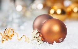Goldene Weihnachtsbälle auf eisigem Hintergrund Lizenzfreies Stockbild