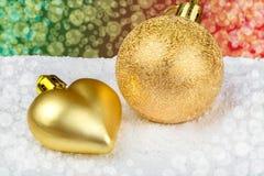 Goldene Weihnachtsdekorationen auf Schnee Lizenzfreies Stockbild