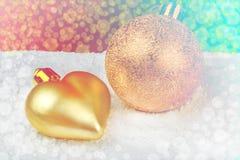 Goldene Weihnachtsdekorationen auf Schnee Stockfoto
