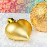 Goldene Weihnachtsdekorationen auf Schnee Stockfotografie