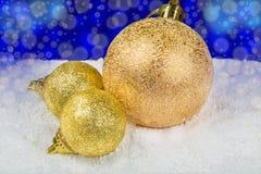 Goldene Weihnachtsdekorationen auf Schnee in Form von Bällen Lizenzfreies Stockfoto