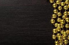 Goldene Weihnachtsgirlande auf schwarzem hölzernem Hintergrund Lizenzfreies Stockfoto