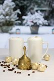 Goldene Weihnachtsglocke und Kaffeetassen Stockfotografie