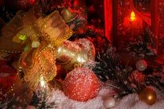 Goldene Weihnachtsglocken und Weihnachtsspielwaren angesichts einer roten Laterne Stockbilder