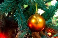 Goldene Weihnachtskugel, die am Zweig hängt Stockfotografie