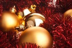 Goldene Weihnachtskugeln auf rotem Filterstreifen stockfotos