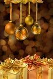 Goldene Weihnachtskugeln und -geschenke Stockfotos