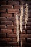 Goldene Weizen- und Roggenohren auf hölzerner Mattierung Lizenzfreie Stockfotografie