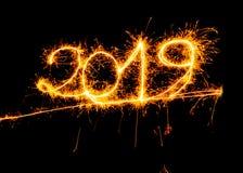 Goldene Zahlen des guten Rutsch ins Neue Jahr 2019 geschrieben mit den Scheinfeuerwerken lokalisiert auf schwarzen Hintergrund stockfotografie