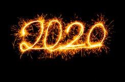 Goldene Zahlen des guten Rutsch ins Neue Jahr 2020 geschrieben mit den Scheinfeuerwerken lokalisiert auf schwarzen Hintergrund stockfotos