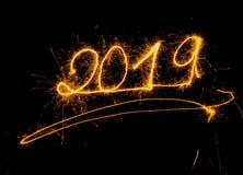 Goldene Zahlen des guten Rutsch ins Neue Jahr 2019 geschrieben mit den Scheinfeuerwerken lokalisiert auf schwarzen Hintergrund stockbild