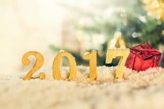 Goldene 2017 Zahlen und rote Geschenkbox im Schnee Stockbild