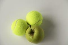 Goldener Apfel mit Tennisbällen Stockfotografie