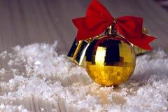 Goldener Ball mit einem roten Bogen Lizenzfreie Stockfotos