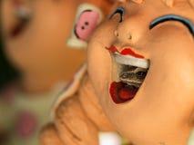 Goldener Baum-Frosch im Mund einer Puppe Stockfotos