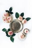 Goldener Behälter der Weinlese, Retro- Platte und Rosarose blühen mit grünen Blättern auf weißem Hintergrund Stockfoto