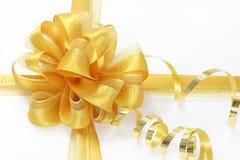 Goldener Bogen mit einem lockigen Farbband lizenzfreie stockfotografie